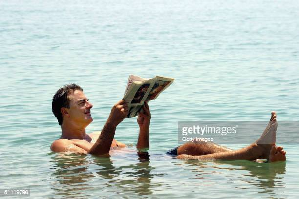 """Sex and the City"""" star, actor Chris Noth, reads a newspaper July 25, 2004 while floating in the theraputic mineral-rich waters of the Dead Sea in..."""