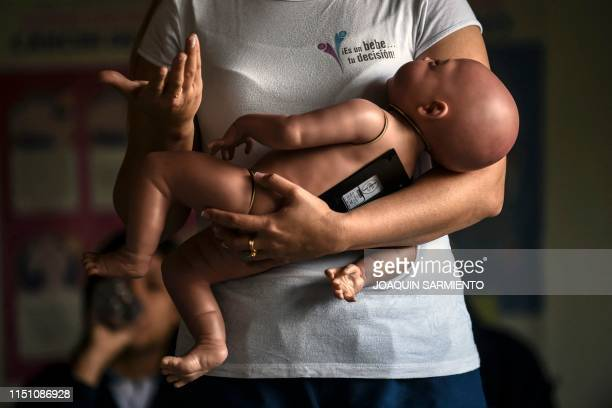 TOPSHOT A sex education teacher shows students how to hold a baby using a baby robot at a school in Caldas Antioquia's department Colombia on May 17...