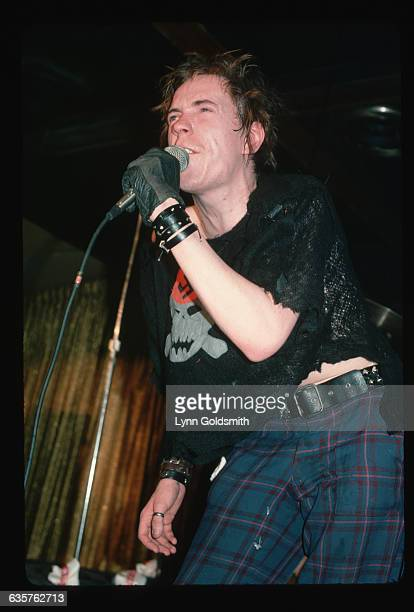 Sex Pistols singer Johnny Rotten on stage performing. He is wearing plaid pants and a black glove.