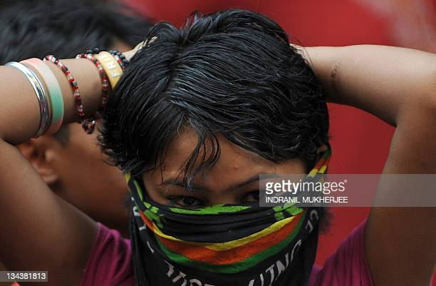 A sex worker covers her face as she watches a skit on HIVAIDS awareness on World Aids day in the city's red light district of Kamathipura in Mumbai...