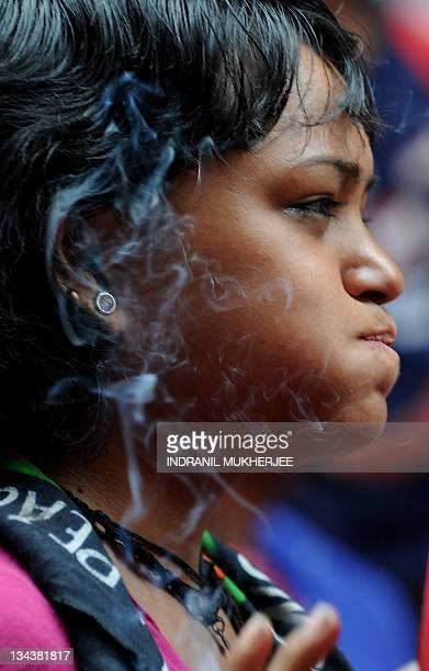 A sex worker smokes a cigarette as she watches performers dance to a popular Bollywood number during a skit on HIVAIDS awareness on World Aids day in...
