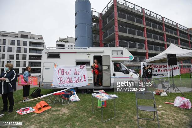 Sex worker stands in a camper with a banner 'Open the brothels now!' during a protest to demand the reopening of brothels amid the new coronavirus...