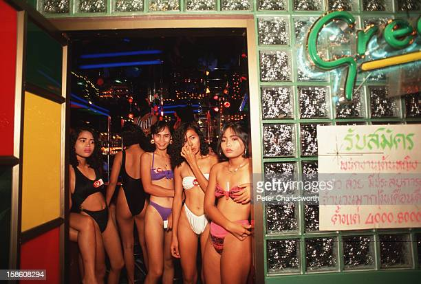 Sex workers crowd a doorway leading into an agogo bar in the redlight district in Pattaya Bar girls dance on stage for customers