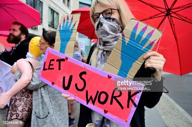 Sex workers hold placards during a protest to demand the reopening of brothels amid the new coronavirus pandemic on July 3 2020 near the Bundesrat in...
