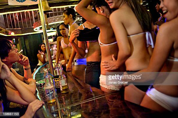 Sex workers in Angeles City line up in front of customers in a bar Many young women in the Philippines end up in prostitution because of widespread...