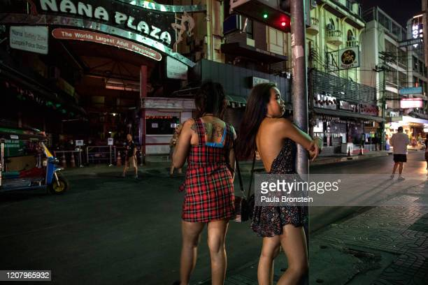 Sex workers stand on the streets of the Nana Plaza area red light districts on March 22 2020 in Bangkok Thailand Thailand's capital imposed a partial...