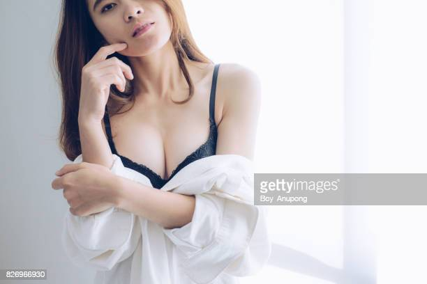 Sexy asian woman standing near the window in the morning.