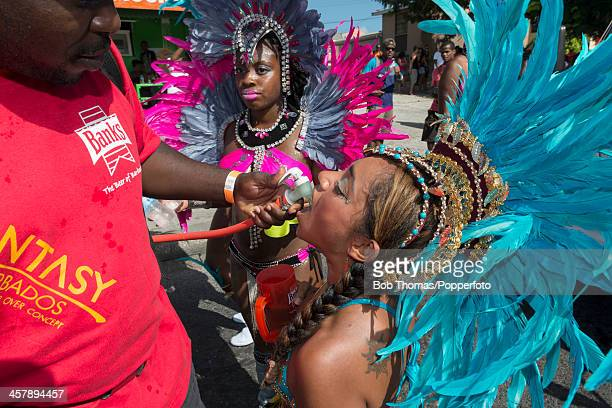 A sexy Bajan girl being 'fueled' with an alcoholic cocktail served by a mobile barman on the road during the Crop Over festival in Bridgetown...