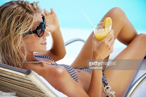 セクシーなビキニの女性、ラウンジチェアに座って、ジュース