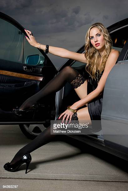 sexy blond in silver car - black dress with stockings foto e immagini stock