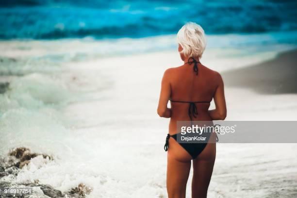 femme blonde sexy en bikini noir, marchant sur la plage - femme blonde en maillot de bain vue de dos photos et images de collection