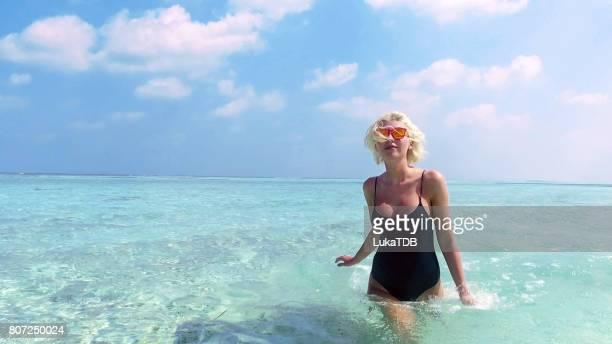 Sexy blonde woman walking through shallow water on Maldives