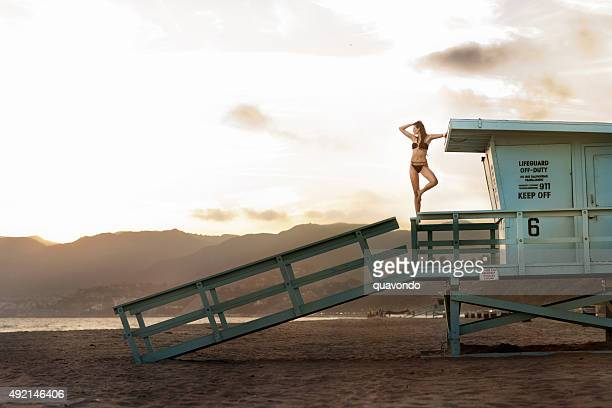Sexy brunette in swimsuit on lifeguard stand