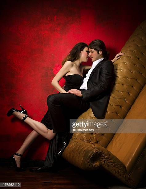 Sexy couple embracing against leather couch
