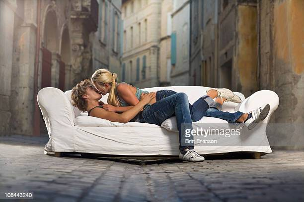 Sexy couple kiss on couch in street