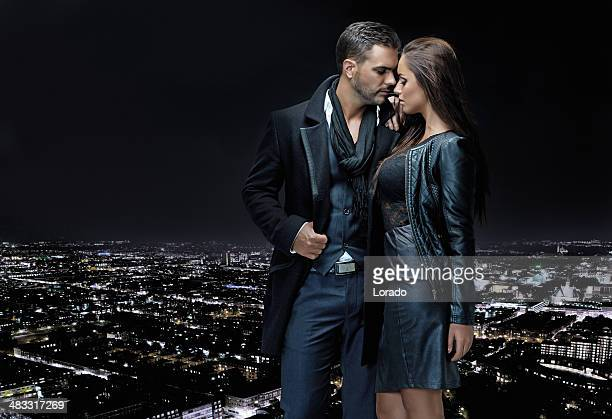 sexy couple posing on top of building in the night
