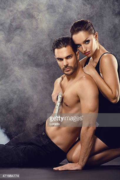 sexy couple posing with gun