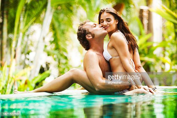 Sexy couple showing affection in the tropical pool.