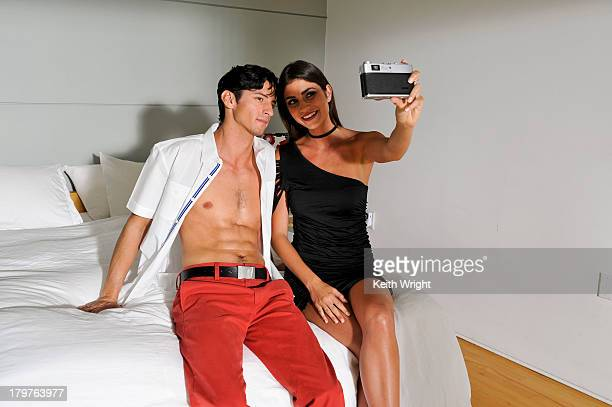 sexy couple taking photos of each other. - アシメトリードレス ストックフォトと画像
