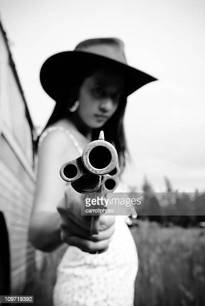 Sexy Cowgirl mit Pistole auf Ihrem Gesicht