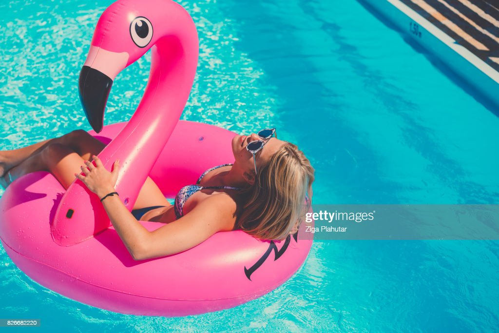 Sexy girl in bikini wearing sunglasses on inflatable flamingo : Stock Photo
