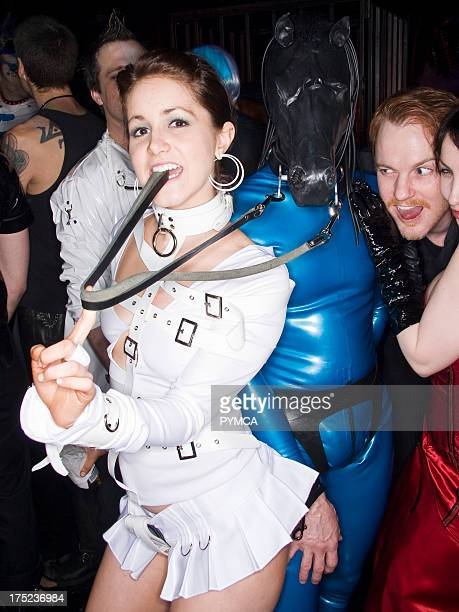 Sexy girl in white latex buckled top and miniskirt holds the reins to a man dressed in latex with a full latex horse head mask Los Angeles USA 2008