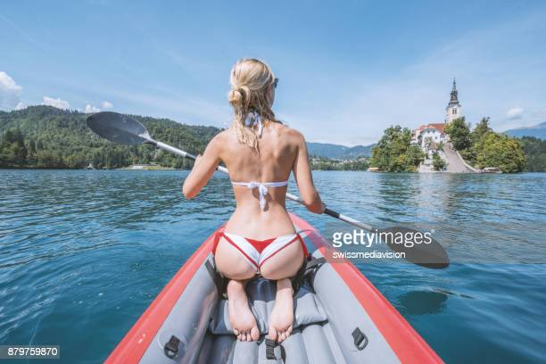 Sexy girl paddling red canoe in Slovenia