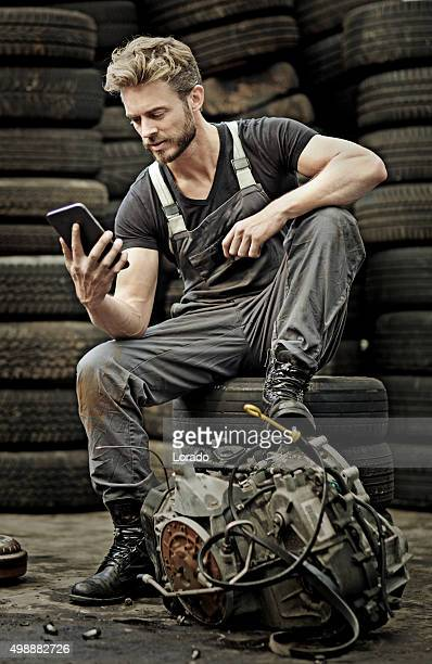 sexy male mechanic using tablet