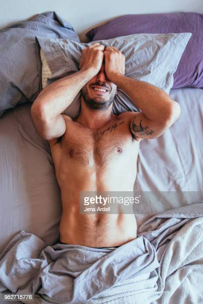 sexy man covering face in bed, sexy man lying in bed - halbbekleidet stock-fotos und bilder
