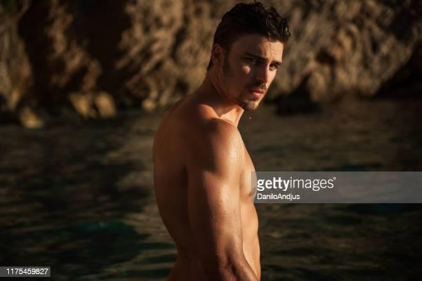 sexy mann am strand im sommer - sinnlichkeit stock-fotos und bilder