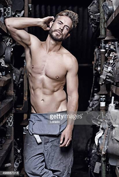 sexy man posing at junkyard