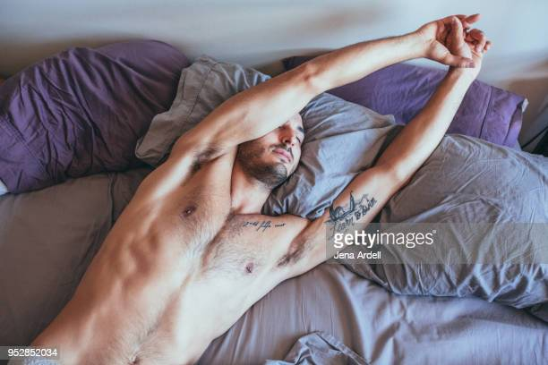 sexy man stretching in bed - brustwarzen piercing stock-fotos und bilder