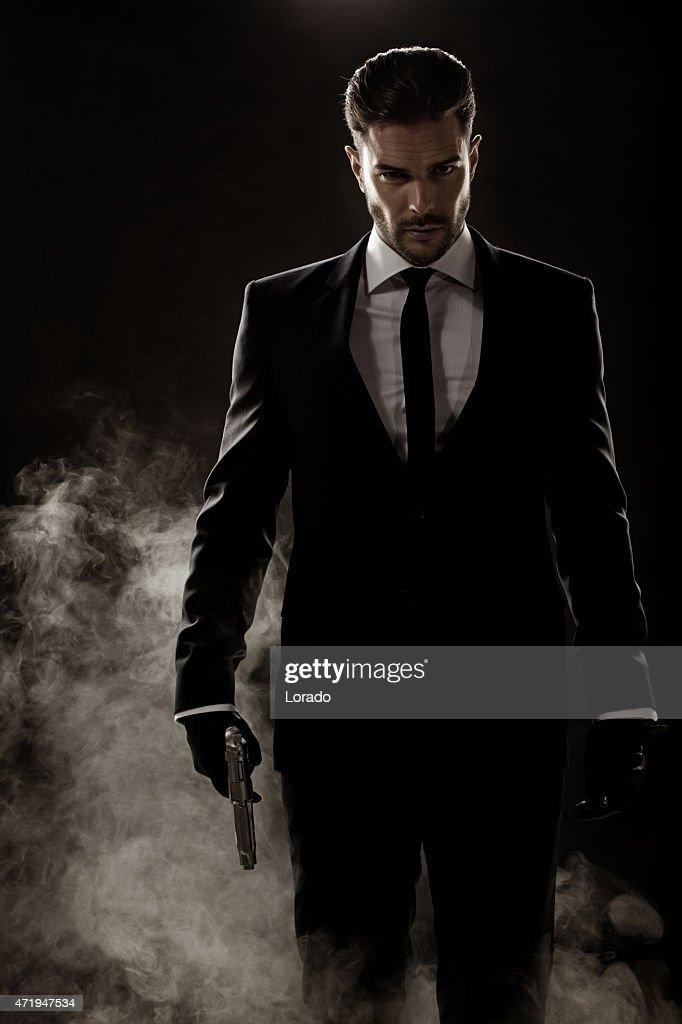 sexy man walking holding gun : Stock Photo