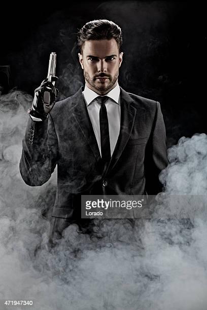 sexy Mann trägt Anzug hält Waffe
