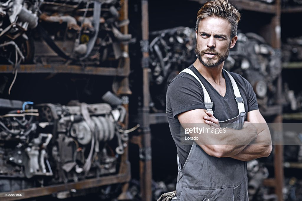 sexy mechanic standing in front of car engines : Stock Photo