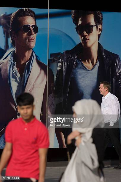 Sexy mens' fashion poster and passing Muslim shoppers at the 2012 Olympic Westfield mall in Stratford, east London. Beneath the giant sized images of...