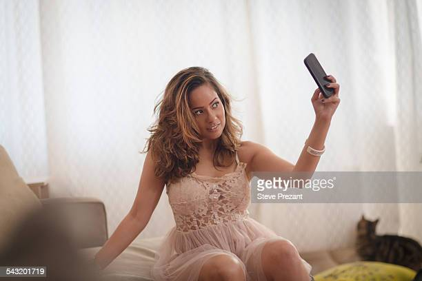 Sexy mid adult woman taking smartphone selfie on living room sofa