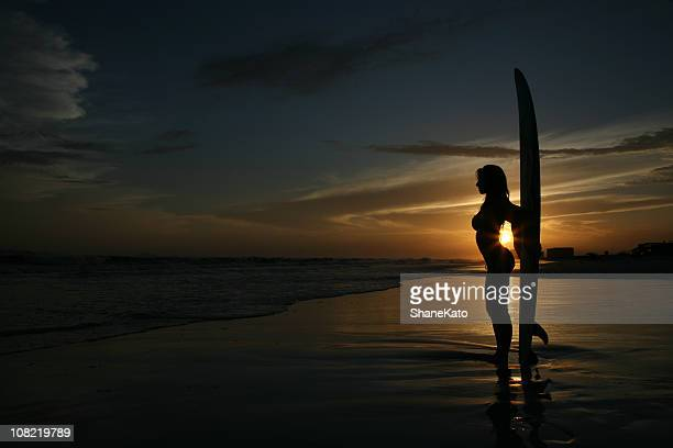 Sexy silhouette surfing sunset at beach