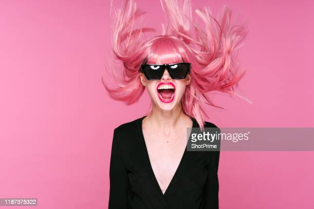 sexy surprised woman in pink wig with flying hair on pink background - lilac fashin stock pictures, royalty-free photos & images