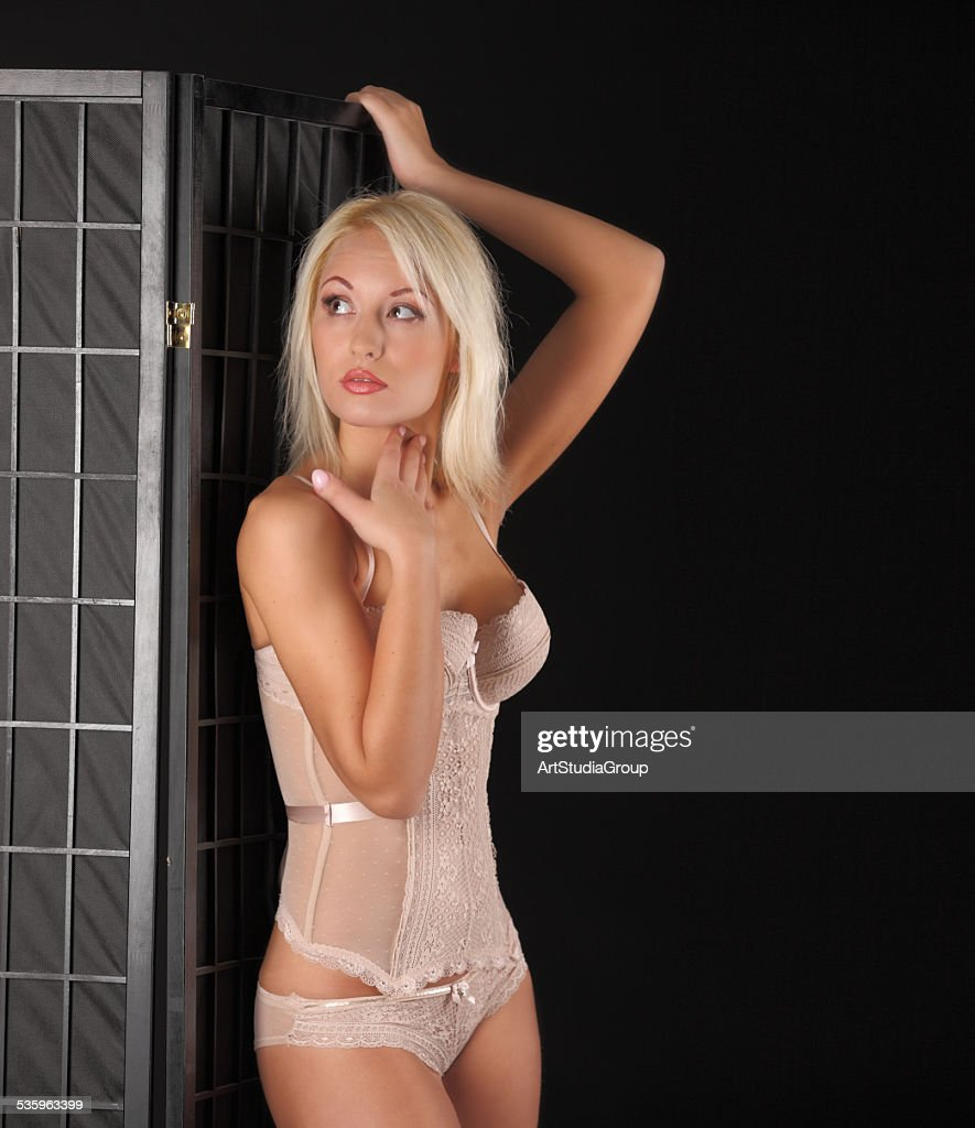 Sexy white haired woman posing in lingerie on black background : Stock Photo