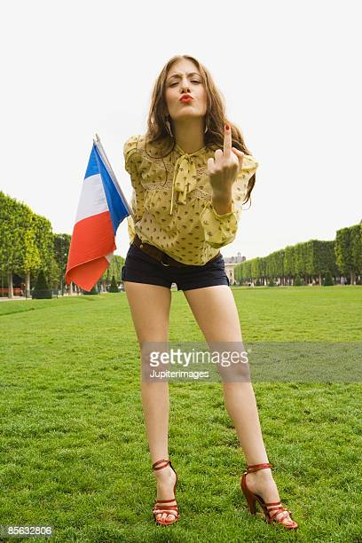 sexy woman holding french flag while giving the middle finger - middle finger funny stock photos and pictures
