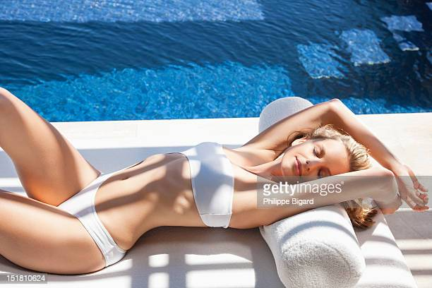 Sexy woman in bikini laying on lounge chair at poolside
