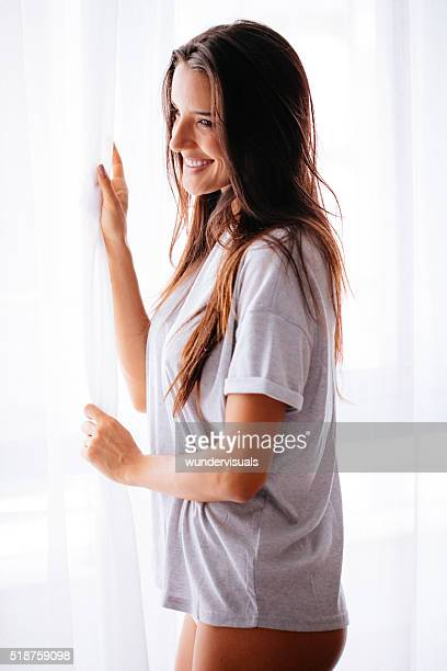 Sexy woman in boyfriend shirt is standing close to window