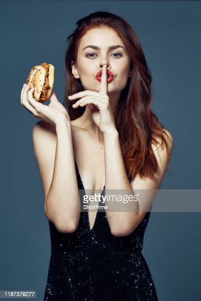 sexy woman in evening dress eating burger - beautiful woman stock pictures, royalty-free photos & images