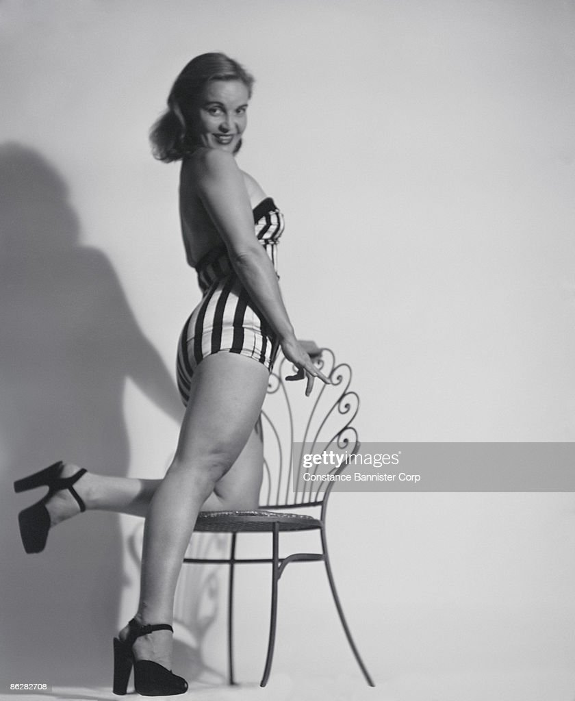 Sexy woman in swimsuit kneeling on chair : Stock Photo