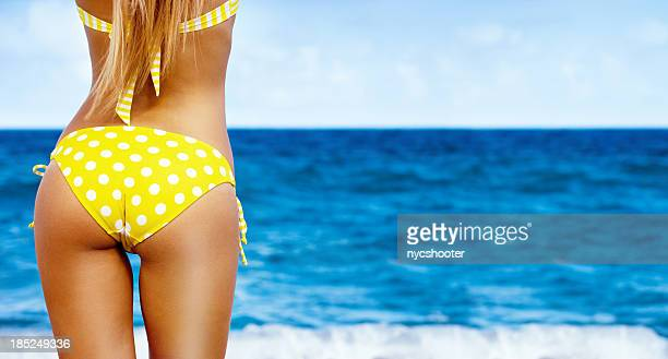 sexy woman in yellow polka dot bikini on beach