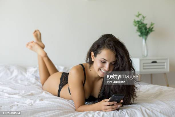 sexy frau liegt auf dem bett mit telefon - verführerische frau stock-fotos und bilder