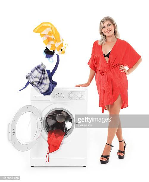 Sexy Frau steht in der Nähe von der Waschmaschine reinigen