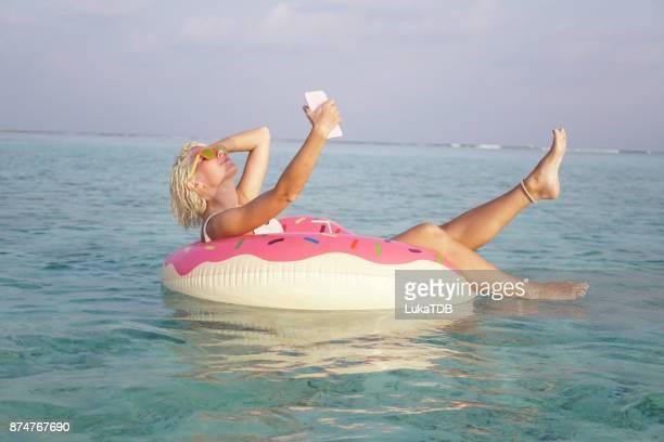 Sexy Frau unter Selfies und trinken Kokoswasser auf den Malediven