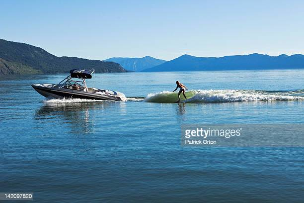 a sexy woman wakesurfs behind a wakeboard boat on a sunny day in idaho. - waterskiing stock photos and pictures